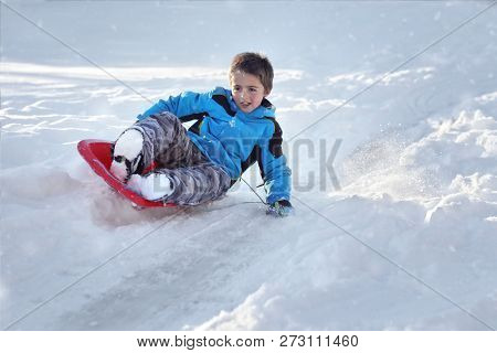 Boy on a sled sledding down a hill in the snow
