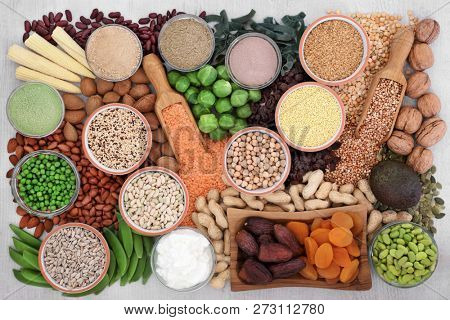 Health food with high protein content with legumes, vegetables, dried fruit, grains, supplement powders, almond yoghurt, seeds & nuts. Super food high in fibre, vitamins & antioxidants. Top view.