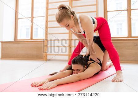 Fitness instructor helping fit girl with difficult stretching exercise on the floor