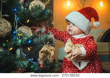 Christmas Babies. Christmas Children. Cute Little Child Is Decorating Christmas Tree Indoors. Happy
