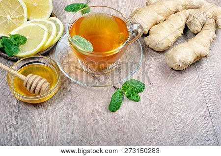 Honey, Ginger, Lemon And Cup Of Tea On The Wooden Table. Cold And Flu Remedy. Close Up.