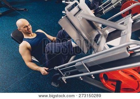 Happy Male Doing Exercise On Training Apparatus. Physical Training Of A Man On A Training Apparatus