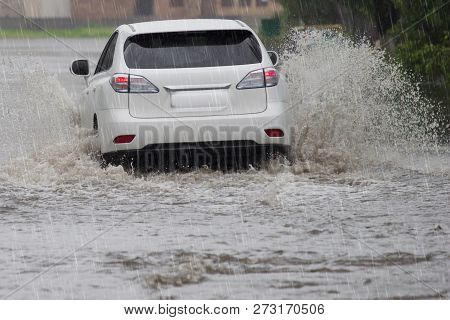 Driving Car On A Wet Street With Splashing Water In Flood Road At Rain Day