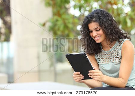 Happy Woman Reading Online Content In A Tablet Or Ebook Sitting On A Bench In A Park