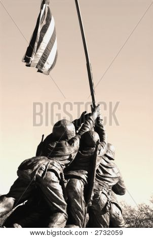 A statue of the men on Iwo Jima holding up the flag. poster