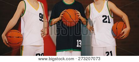 Kids Basketball Team. Young Basketball Players Holding Balls On Basketball Court. Basketball Horizon