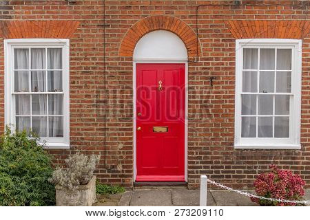 Typical English House Facade With Red Door, Two White Windows And Bricks Wall Viewed From Outdoors.