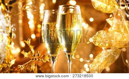 Holiday Champagne over Golden glow background. Christmas and New Year celebration. Two Flutes with Sparkling Wine. Champagne over Holiday gold Bokeh Blinking Background. Table setting, decoration