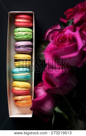 Sweet colorful macaroons and roses on black background.