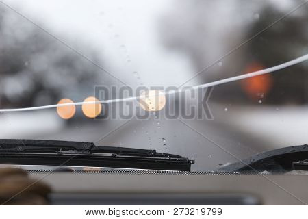Vehicle Windshield Or Windscreen With Large Crack In Focus. Cars And Road Blurred In Background.
