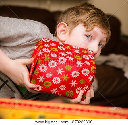 Young Boy Holds A Wrapped Gift Excitedly On Christmas Morning.
