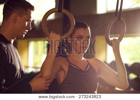 Fit, Sporty And Athletic Sportswoman Working In A Gym. Woman Training Using Gymnastic Rings. Sports,