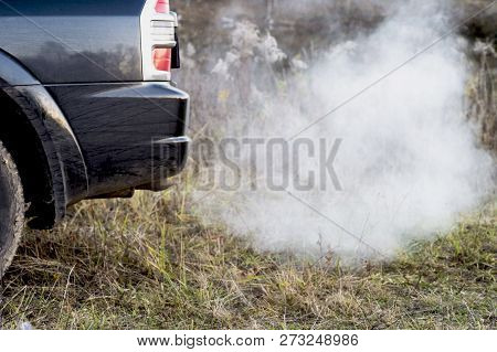 The Back Of The Black Car With The Emission Of Smoke From The Exhaust Pipe On The Background Of Natu