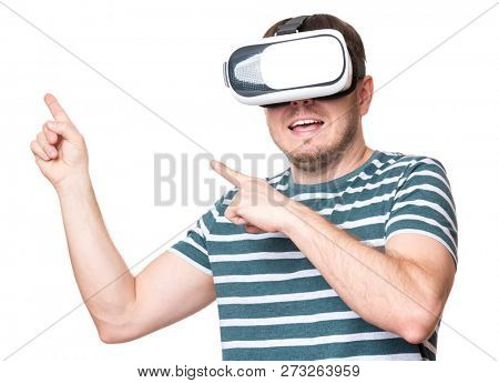 Happy man wearing virtual reality goggles watching movies or playing video games gesticulating hands, isolated on white background. Smiling male looking in VR glasses.
