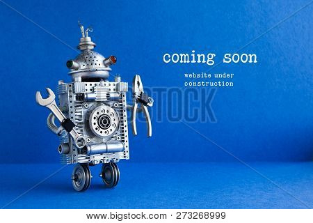 Web Site Under Construction Coming Soon Page. Toy Robot With Hand Wrench And Pliers. Blue Background