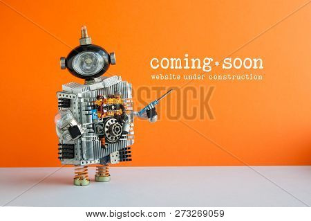 Web Site Under Construction Coming Soon Page. Toy Robot With Screwdriver And Light Bulb. Orange Wall