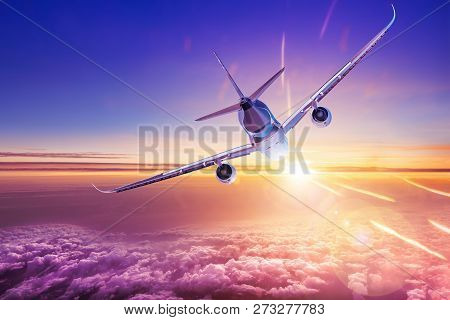 Commercial Airplane Over The Clouds Flies Into The Sun