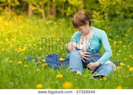Little baby girl breast feeding outdoor