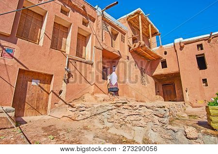 The typical street of Abyaneh village with preserved red adobe houses, located on the slope of Karkas mount, Iran. poster