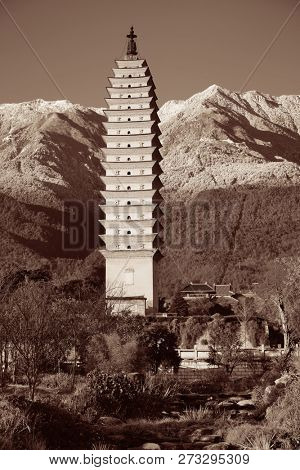 Ancient pagoda in Dali old town with snow capped Mt Cangshan, Yunnan, China.