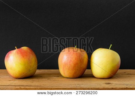An image of a black background three apples wooden table