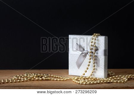 A holidays decoration gift box with golden pearls on black background