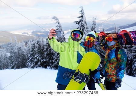 Three Snowboarders Taking Selfie With Smartphone Camera At Ski Resort. Friends Photographing For Soc