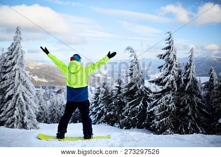 Snowboarder Raised His Arms And Hands To The Sky At Ski Resort. Man Climbed A Mountain Top Through F