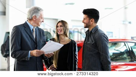 Car dealer reading a contract to a couple in an auto showroom