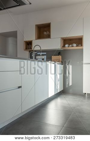 Sunny Modern Kitchen With White Walls And Tiled Floor