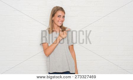 Beautiful young woman over white brick wall cheerful with a smile of face pointing with hand and finger up to the side with happy and natural expression on face looking at the camera.