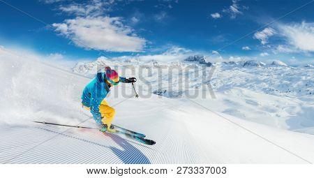 Alpine skier skiing downhill, panoramic format. Winter sports and leasure activities