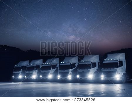 New Haulage Truck White Fleet Is Parking At Night With Astronomy Milkyway On Teh Sky Landscape View.