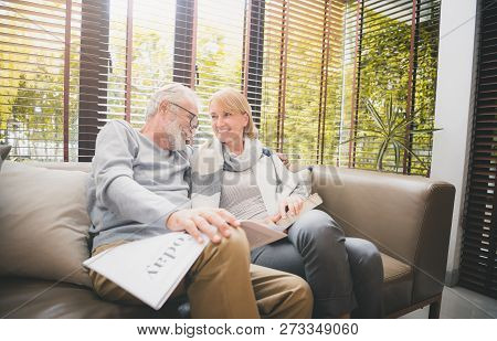 Happy Senior Couple Sitting At Sofa In Living Room And Reading A Book,newspaper Together. Take A Mom