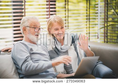 Happy Grandparents Are Talking To Their Children Through A Notebook At Home. Take A Moment Of Happin