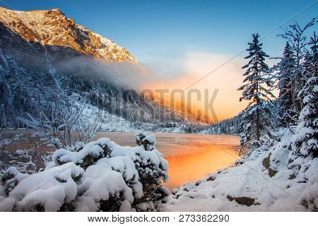 Winter Nature In Mountains At Morning Sunrise. Bright Sunlight Reflected In Mountain Lake. Snowy Lan