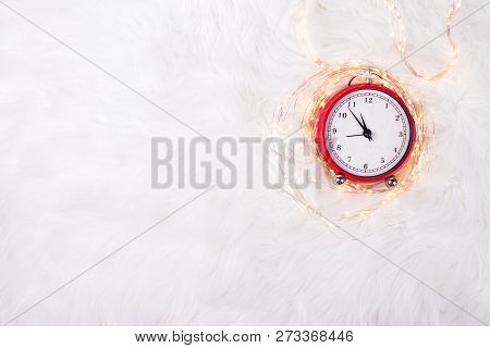 Red  Alarm Clock - Symbol Of  New Year And Fairy Lights  On White Fur Background. Winter Holidays Co