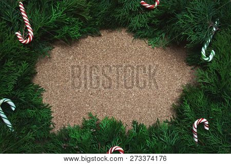 Frame Of Conifer Branches And Candy Canes On A Cork Board. Christmas