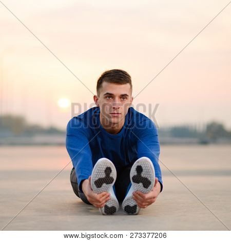 Young Male Runner Stretching and Preparing for Runat Sunset. Healthy Lifestyle and Active Sport Concept.