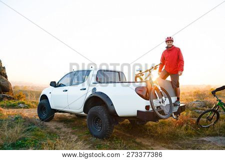 Cyclist Getting Ready for Bike Riding with Friends and Taking the Bicycles off the Pickup Offroad Truck in the Mountains at Warm Autumn Sunset. MTB Adventure and Car Travel Concept.