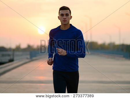 Young Sports Man Running at Sunset. Healthy Lifestyle and Active Sport Concept.
