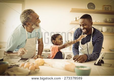 Smiling multi-generation family with flour on the nose standing in the kitchen