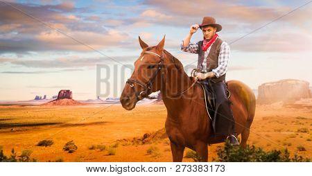 Cowboy riding a horse in desert valley, western
