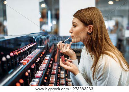 Female customer testing lip liner in make-up shop