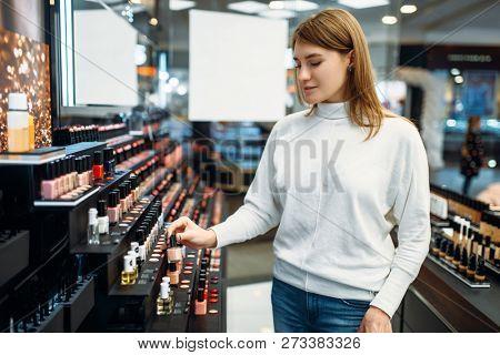 Female customer looking cosmetics in makeup shop