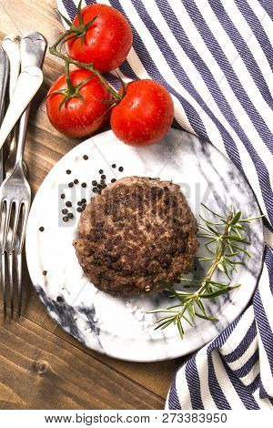 Grilled Northern Ireland Beef Burger Patty With Reduced Fat On Marble And Fresh Wet Tomato