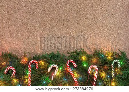 Christmas Background With Conifer Branches, Colorful Lights And Candy Canes On A Cork Board