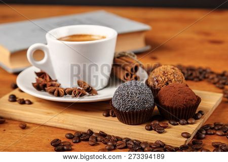 Coffee Break A Cup Of Hot Coffee And Cakes On A Wooden Table With A Book. A White Cup Of Black Coffe