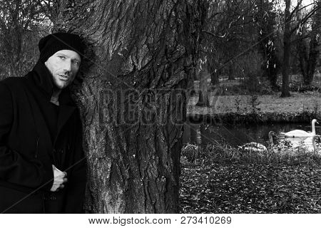 Black And White Portrait Of Handsome Man Leaning Against Tree In Park With Swans In Background