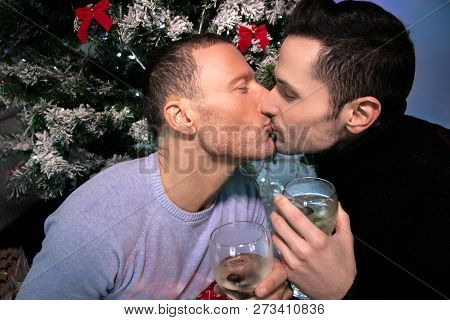 Happy Male Gay Couple Celebrating And Kissing In Front Of Christmas Tree With Glasses Of Wine